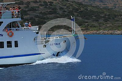 Pleasure boat with tourists on the deck is moving at full speed along the coast. Crete, Greece