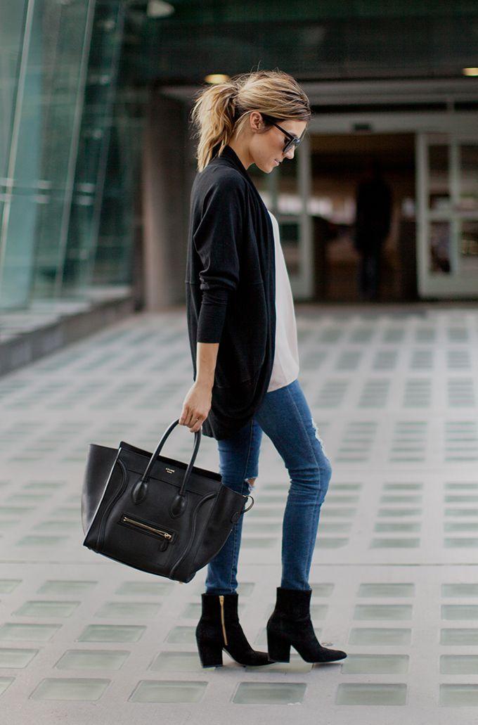 Comprar ropa de este look:  https://es.lookastic.com/moda-mujer/looks/cardigan-abierto-blusa-sin-mangas-vaqueros-pitillo-botines-bolsa-tote-gafas-de-sol/5979  — Gafas de Sol Negras  — Cárdigan Abierto Negro  — Blusa sin Mangas Blanca  — Bolsa Tote de Cuero Negra  — Vaqueros Pitillo Desgastados Azules  — Botines de Ante Negros