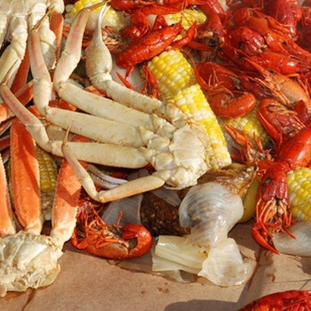 Toss crab legs, lobster and corn into a pot of boiling water.