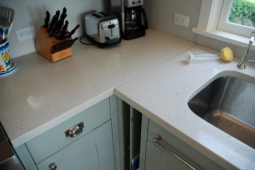 Honed white concrete countertops re-create the look of soft white sand. The areas near the perimeter have been slightly ground down to show off the glints of sea glass aggregate in the concrete.     Countertops: Slab Lab