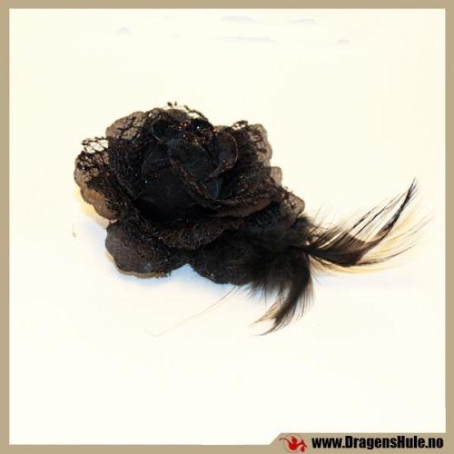 En fin kunstig blomst laget i stoff, med litt glitter og fjær. Bakpå er det både en hårspenne og en sikkerhetsnål, så man kan enten ha den i håret eller bruke som en brosje eller en button. Mål: Selve blomsten er ca 6-7cm i diameter, og ca 4cm tykk. I tillegg kommer det noen cm med fjær her og der, som vil variere fra hårpåynt til hårpynt, Hårspennedelen er ca 4cm lang.