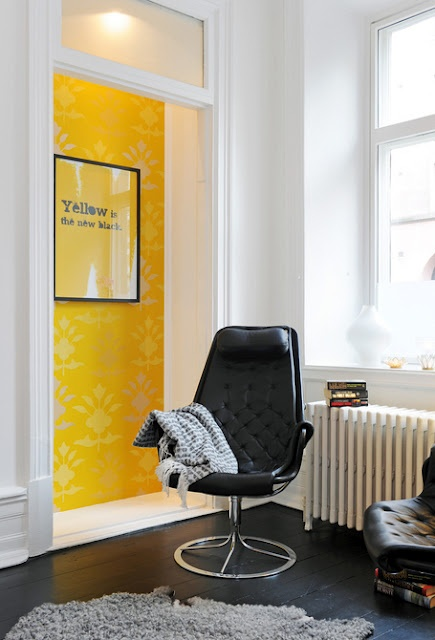 YELLOW is the new black poster. Yellow accent wal, black chair and floor, lovely room and light.