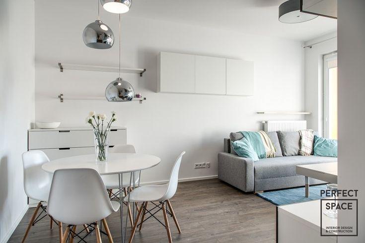 Aranżacja salonu w nowoczesnym stylu. Jasny i przytulny salon gdzie dominuje biel z akcentem błękitu.