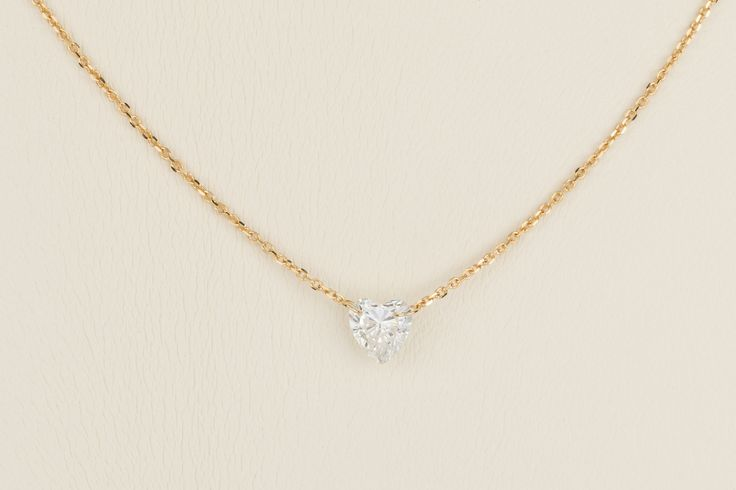 A pretty heart shaped diamond necklace with a .453ct central diamond swinging from a very fine 18k yellow gold trace link chain. So delicate!