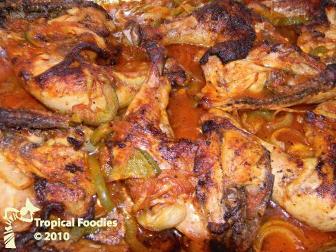Haitian recipe: Chicken in sauce      1 Medium chicken or 6 whole chicken thighs     1 lime or lemon     Chopped garlic (taste)     Salt and pepper     Ground cloves     4-5 tablespoons oil     1 Large onion sliced in rounds     2 green bell peppers (sliced)     1/3 cup tomato paste ((approximately))     3/4 cups water ((approximately))     1 hot pepper ((optional, to taste))