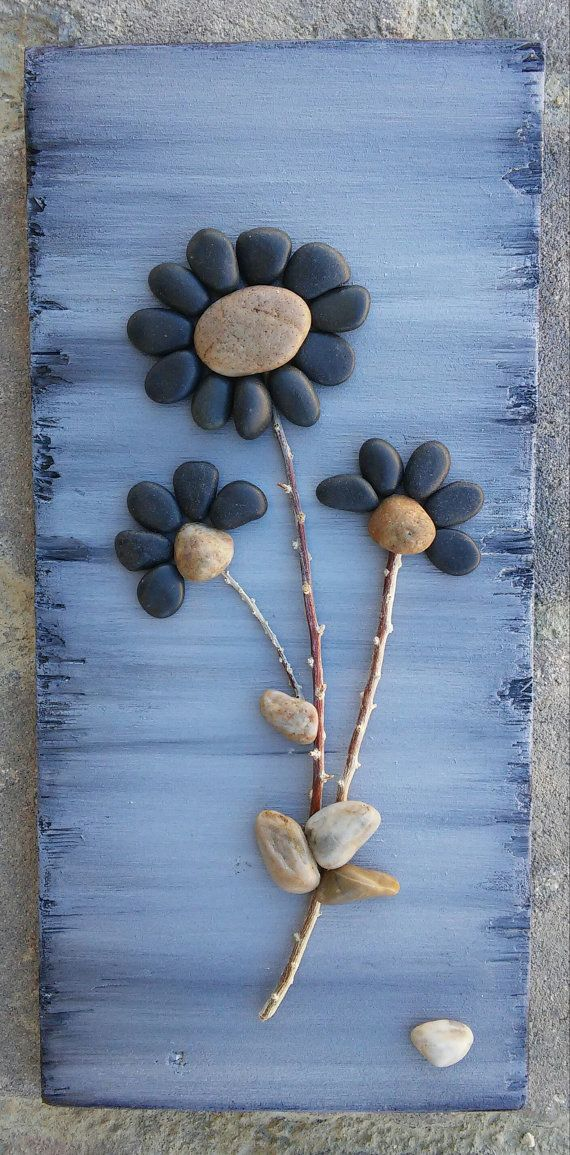 FREE SHIPPING  Beautiful original piece created from all natural materials. The flowers petals are black little pebbles, and the stems are twigs. The reclaimed wood was painted in acrylics, and sprayed lightly with sealant to give it a shiny appearance. The back/reverse side is also painted, and is ready to hang on a wall.  Approx measurements are 12 inches long and 5.5 inches wide.  I always love special requests, and this type of work is wonderful for any occassion or gift idea. If you…