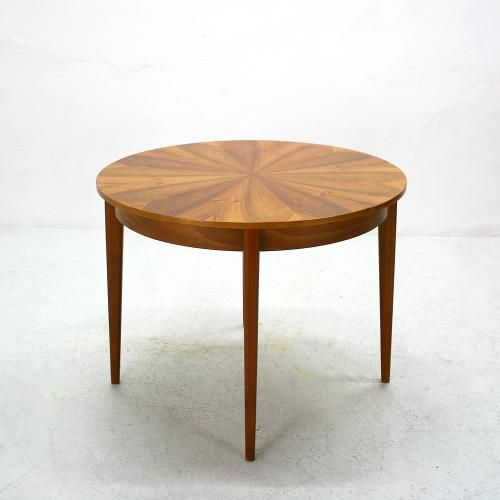 this classic round extendable dining table from the 60s has a star shaped walnut