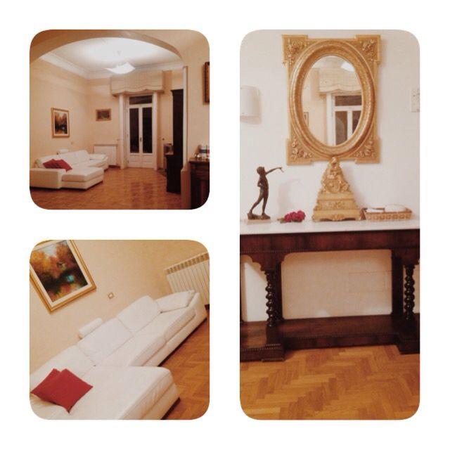 Arredamento: divano bianco di pelle; mobile adornato con un orologio color oro e una statuetta di bronzo scuro stile antico '700; veduta complessiva del salone.