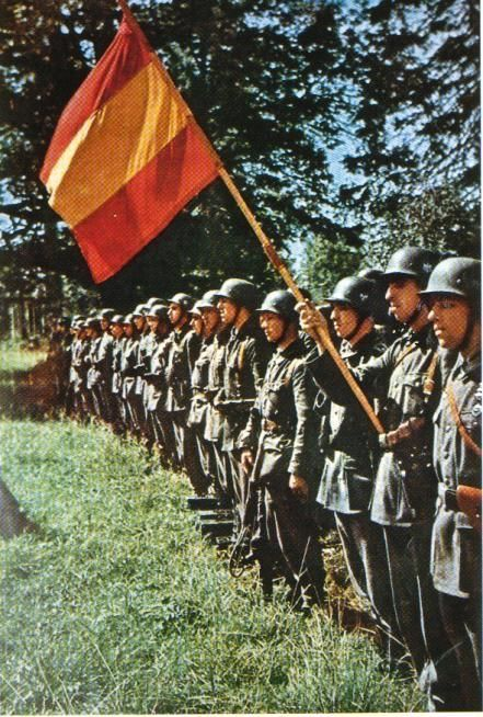 Soldiers of the Blue Division, an expeditionary force sent by Generalissimo Francisco Franco of Nationalist Spain to aid in the German war effort, stand in formation wielding a banner of Spain's national colors as part of a military drill. Eastern Europe, Summer 1941. The division was officially part of the German Wehrmacht but answered to Franco overall.
