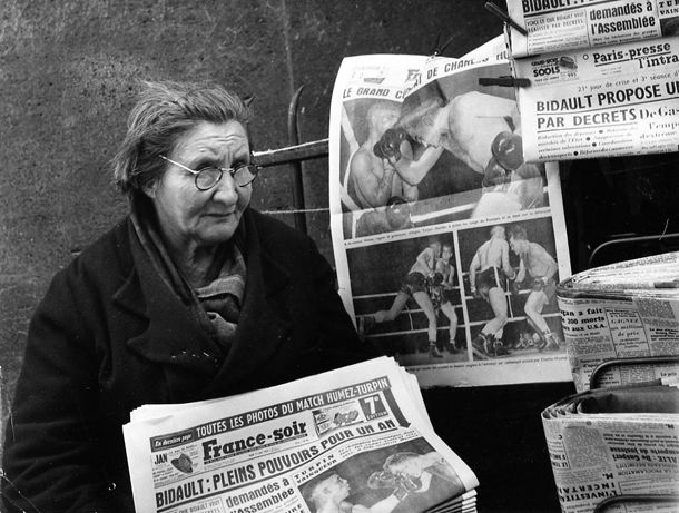 Atelier Robert Doisneau | Site officiel // Woman selling newspapers to the metro Passy, 1953 in Paris, France. ( http://www.gettyimages.co.uk/detail/news-photo/passy-metro-station-news-photo/121512302