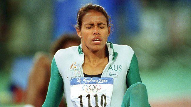 Cathy Freeman slumps to the track physically and emotionally
