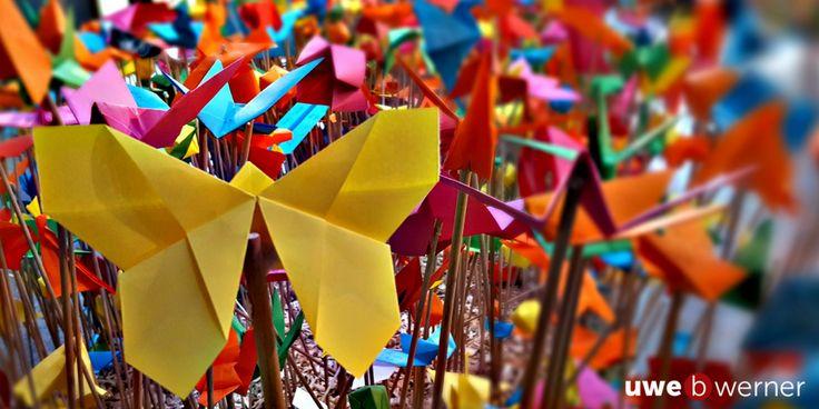 Bei einem Besuch im Berliner Bikini HausBerliner Bikini Haus, nahe der GedächtniskircheGedächtniskirche, entdeckte ich ein wunderbares Farbenmeer, welches sich bei näherer Betrachtung als eine Vielzahl von gefalteten und beschrifteten Objekten aus Papier entpuppte.