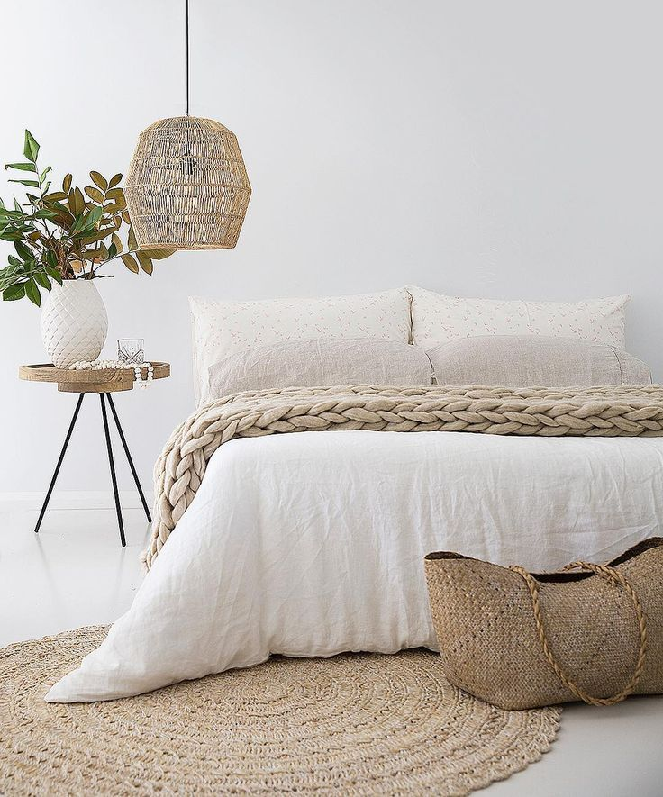 Bedroom with neutral colors and natural products - sisal rug, linen duvet and rattan accessories