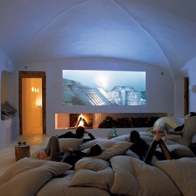 a fire place large projector screen and a dozen fluffy pillow make up a matchless