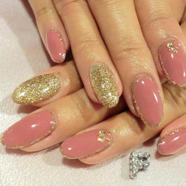 Want to look fabulous and glamorous all the time? Don't hesitate to get the glam nails when you want to go out shopping and simply flaunt your beautiful long nails to the public. The pretty dark nude shade blends well with the gold glitter nail powers that playfully cover and line the edges of the nails for ornament.