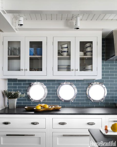 "How cool are these portholes? A ""fisherman's shack"" stays true to its roots with authentic porthole windows set in Ann Sacks's Jute glass tile. Honed granite counters look like slate but withstand more wear and tear. For more beautiful kitchen inspiration, click through the gallery."