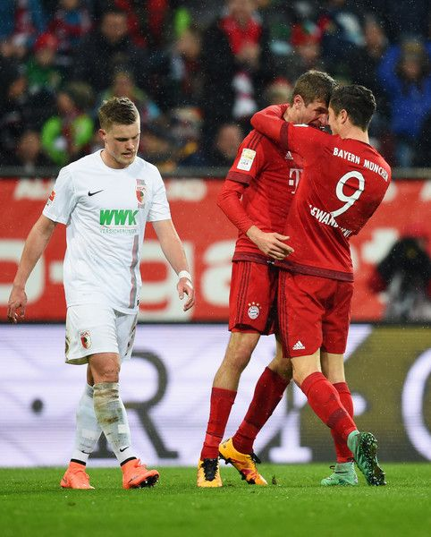 Thomas Mueller Photos Photos - Robert Lewandowski of Bayern Munich (9) celebrates with Thomas Mueller as he scores their first goal during the Bundesliga match between FC Augsburg and FC Bayern Muenchen at SGL Arena on February 14, 2016 in Augsburg, Germany. - FC Augsburg v FC Bayern Muenchen - Bundesliga