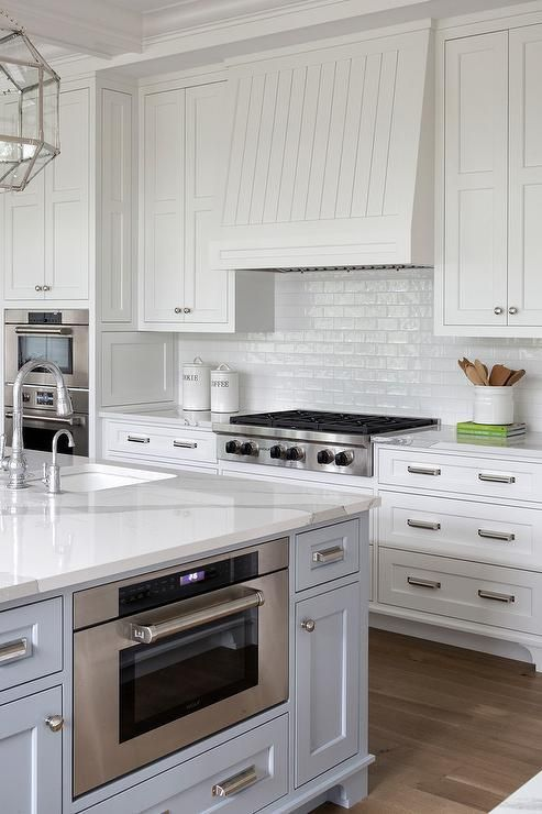 White cabinets accented with polished nickel knobs flank a white vertical beadboard kitchen hood mounted to white glazed backsplash tiles over a stainless steel gas integrated cooktop.
