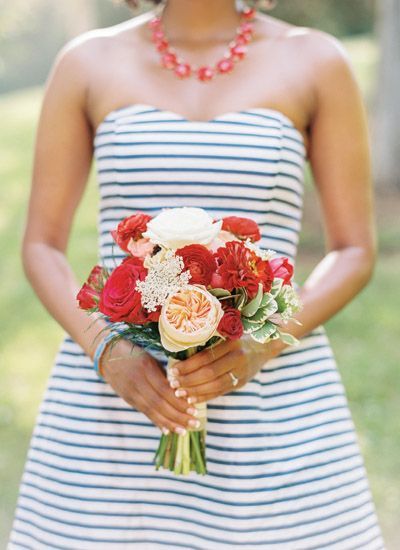 Bridesmaid bouquet filled with red, peach and white flowers.