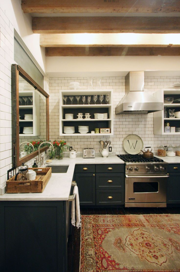 mirror above the sink, dark cabinets, subway tile, vintage rug