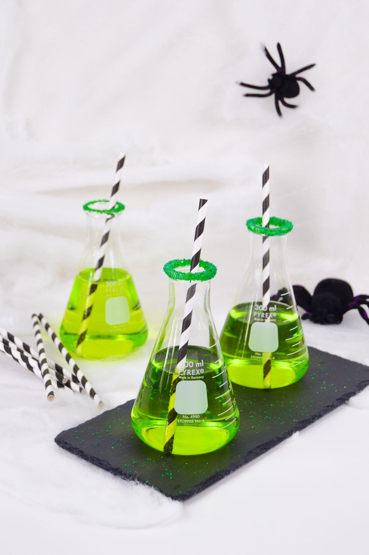 Make these DIY green chemical cocktail for Halloween with Midori, vodka, rum and champaign in a beaker to create a chemical-like creation.