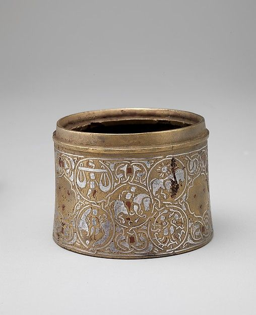 Inkwell with twelve Zodiac medallions. Date: late 12th–early 13th century. Geography: Iran. Culture: Islamic. Medium: Brass; cast, inlaid with silver and copper. Dimensions: H. 2 3/8 in. (6 cm) Diam. 3 1/4 in. (8.3 cm). Accession Number: 44.131. On this vessel, the signs of the Zodiac are arranged in groups of four, surrounding a central medallion with a horseman or a falconer.