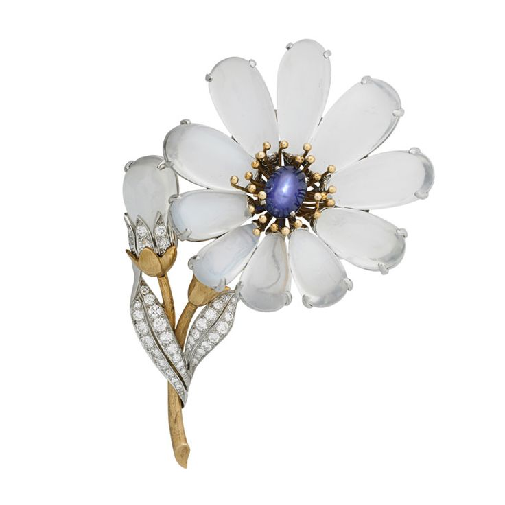 """MARCUS & CO. STAR SAPPHIRE & MOONSTONE FLOWER BROOCH Estimate: $7,000 - $9,000   With dimensional moonstone cabochon petals and bud, central oval blue star sapphire, approx. 4 cts. by formula, wire and shot work filament and conforming platinum and OEC diamond leaves, approx. 1.10 cts. TW, on hand engraved yellow gold stem. 18k. Ca. 1939. Marked Marcus. 3"""" x 2 7/8"""". 28.5 dwt."""