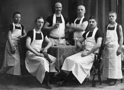 This image shows a German Master Butcher (center with mustache) with his companions. Left and right outside are the two apprentices. The companions have their personal tools on a belt. The photograph was taken in 1917 in Recklinghausen, Germany.