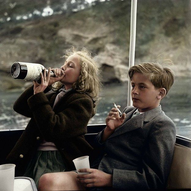 Two young children have a drink and smoke aboard a boat in 1955. | 20 Historic Photos Shown In Extraordinary Color