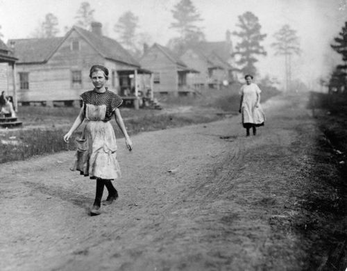 A young girl employed by a cotton mill walks past the frame houses of other workers on her way to the mill. Mississippi, 1913.