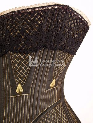 Black front busk corset, 1875: Lace and stitching