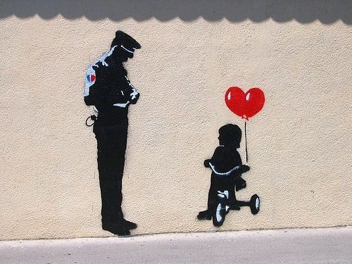 street art . Bansky . Officer writing citation for tricycle.  000