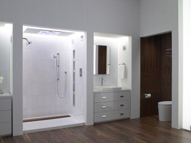 Badkamer met houten vloer. Een badkamer voor de echte doucheliefhebber! Opvallend is dat alle functies (wastafel, toilet en douche) duidelijk van elkaar gescheiden zijn waardoor de badkamer een strenge en opgeruimde indruk maakt. De douche, die de grootste nis heeft gekregen, heeft een teakhouten drain. De douche is verder minimalistisch maar wel heel luxe uitgevoerd. Naast de handdouche beschikt deze douche over een vaste douchekop en een regendouche in het plafond. Een smalle maar hoge nis…