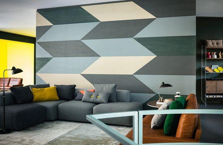 salon aménagé avec un canapé d'angle gris et décoré d'une peinture décorative géométrique