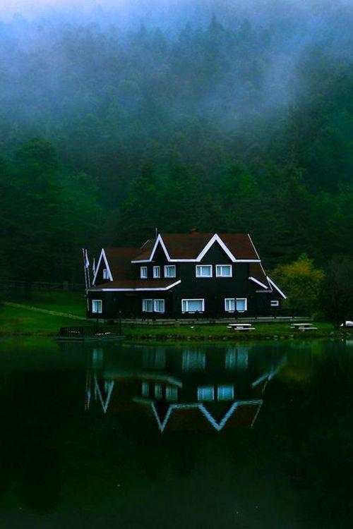 the warm summer sky and seasonal fog reveals the lake house in turkey, bolu.