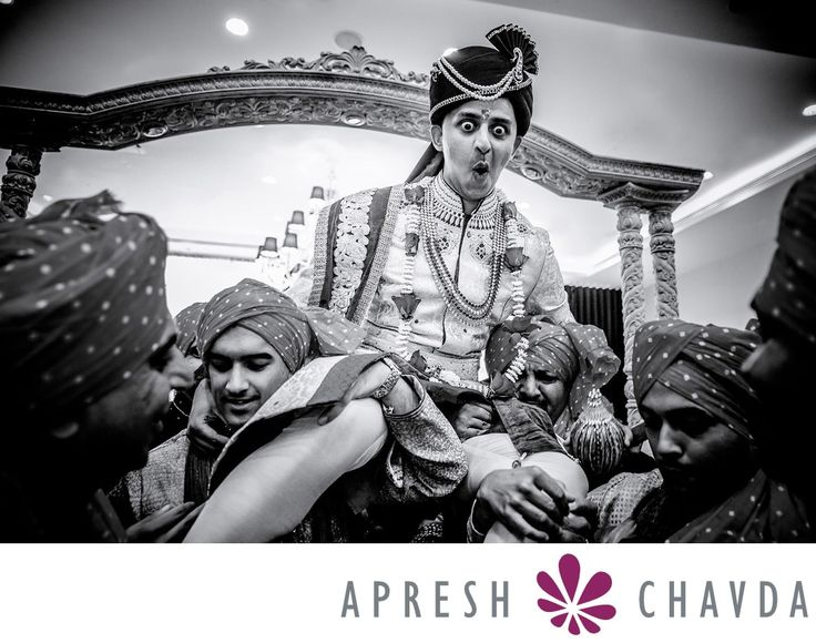 Asian Wedding Photographers London: Indian, Hindu Wedding Photography, Sikh Wedding Photography - hilton syon park wedding photographer: This is one of my favorite images of the groom arriving for a hindu wedding ceremony. The bride's sisters and cousins will attempt to steal the groom's shoes before his entrance into the mandap. As you can see the groom here was lifted up by his best men to protect his shoes.The expression on his face says it all. If stolen by the bride's side, the shoes…