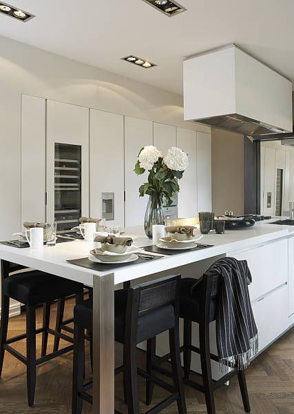 stylish white contemporary kitchen with space to dine s/steel posts on breakfast bar