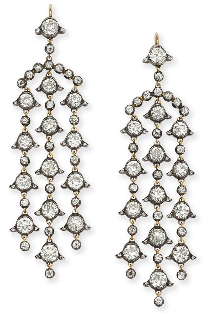 A pair of diamond pendant earrings  Of chandelier form and composed of three rows, each old brilliant-cut diamond set within stylised foliate collets to similarly cut diamond collet spacers, suspended from an arc of collet-set diamonds to a further diamond surmount, length 7.5 cm.