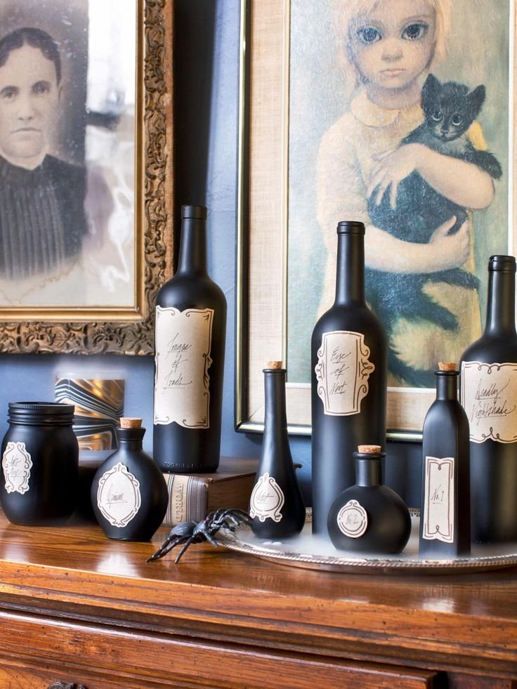Hip Halloween Decorating Idea | Don't toss that empty bottle. Instead make it part of your spooky Halloween decor. A little spray paint and some blank labels transform mismatched bottles into an elegant Halloween bar-top vignette.