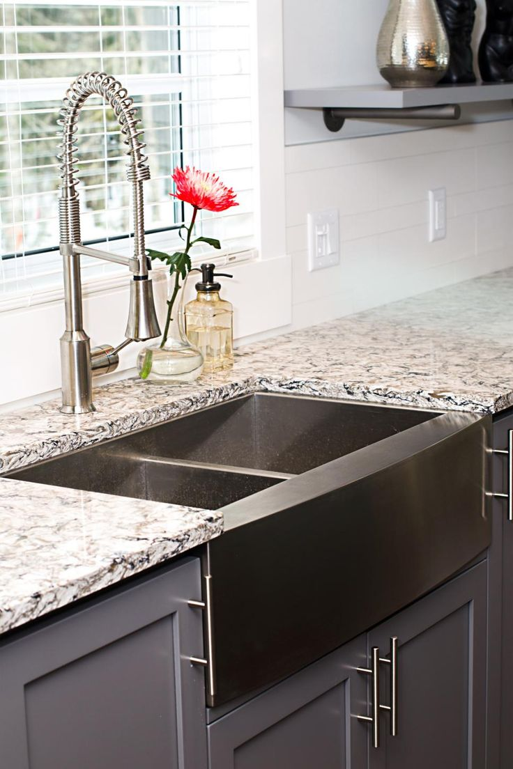 The stone countertop in this kitchen contrasts with the dark cabinetry, and the stainless steel apron-front sink makes a statement and coordinates with the appliances.