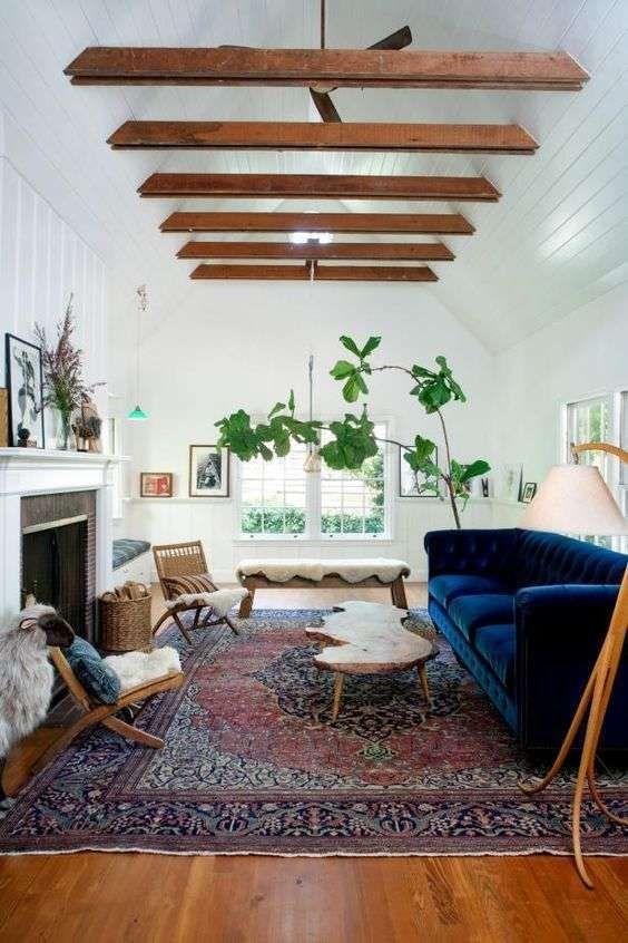 Arredi in legno e divano blu - Salotto in stile rustico con elementi in legno e divano in velluto blu intenso