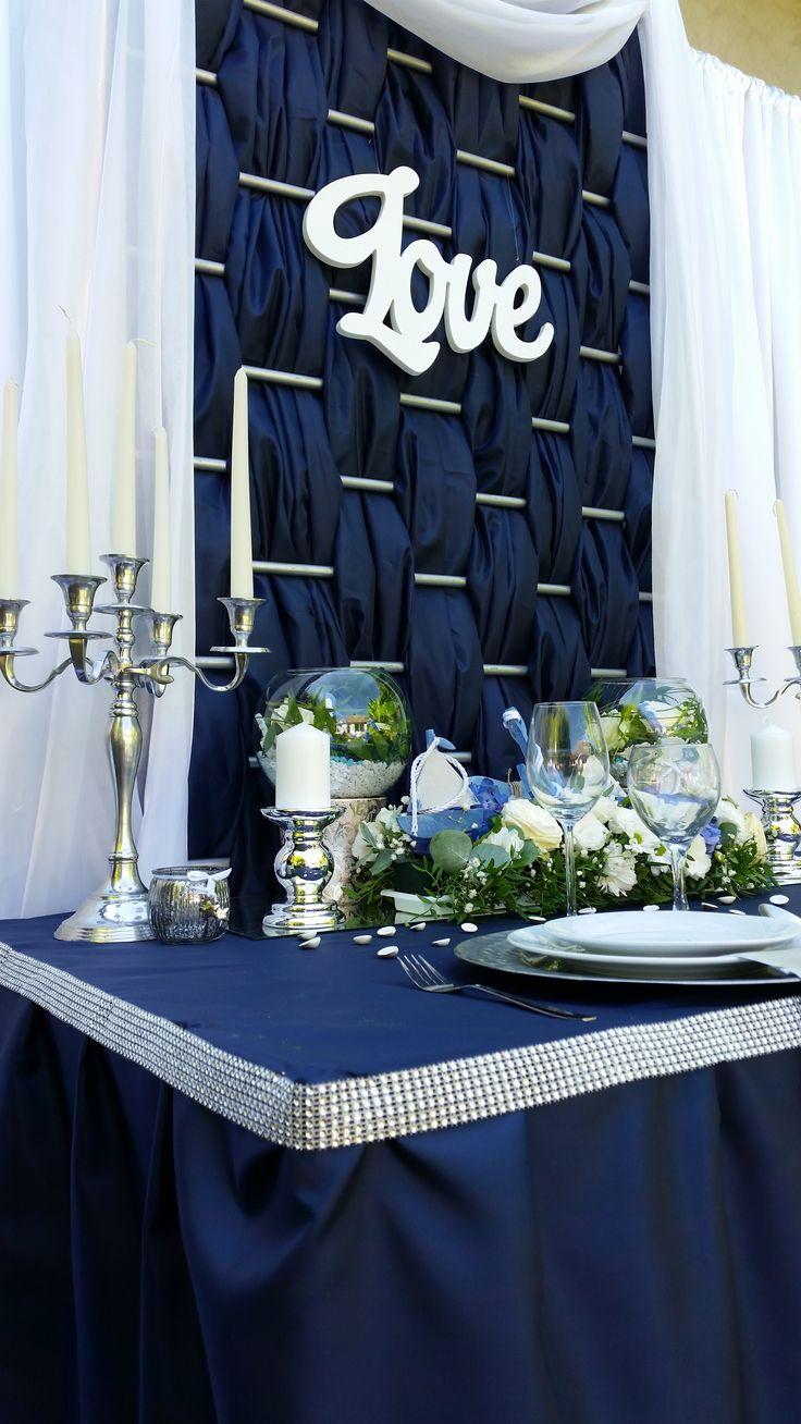 Esküvői dekorációnál érdemes egy fajta vonalvezetést használni. A háttér vízszintes vonalvezetése , visszaköszön az asztal szegésénél is.