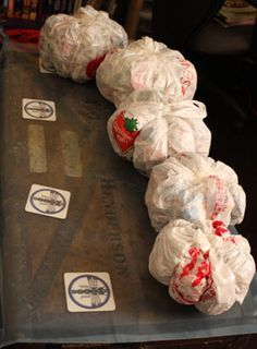 Making paper mache pumpkins. Fill plastic bags with shredded paper and tie string tightly around before paper mache
