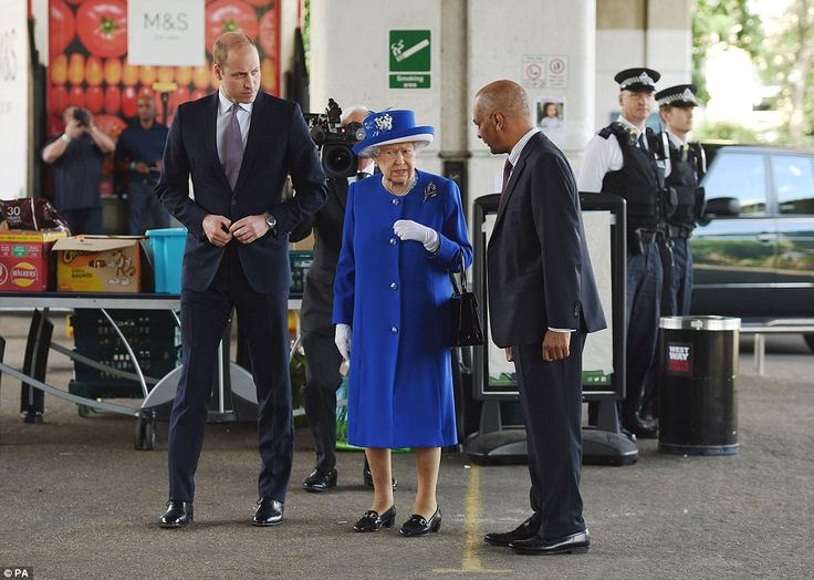Queen Elizabeth II arrived at the centre wearing a blue outfit and matching hat as she talked solemnly with volunteers and officials
