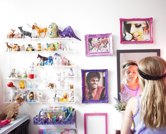 Cool colourful frames and shelf ledges decorate the wall in this little girl's room.