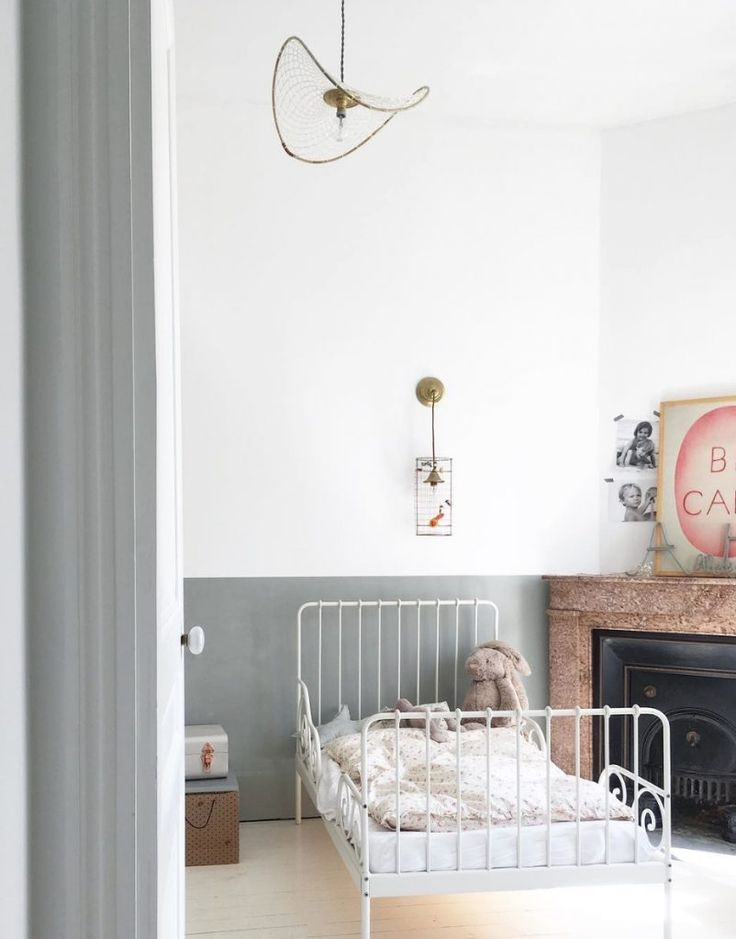 simplistic, modern and feminine little girls room with eclectic lighting, white metal frame bed, and soft pink accents