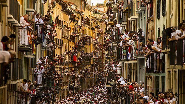 - Espectadores se espremem em sacadas de predios em uma rua de Pamplona, durante o festival de San Fermin, na Espanha. Foto: Andres Kudacki / AP