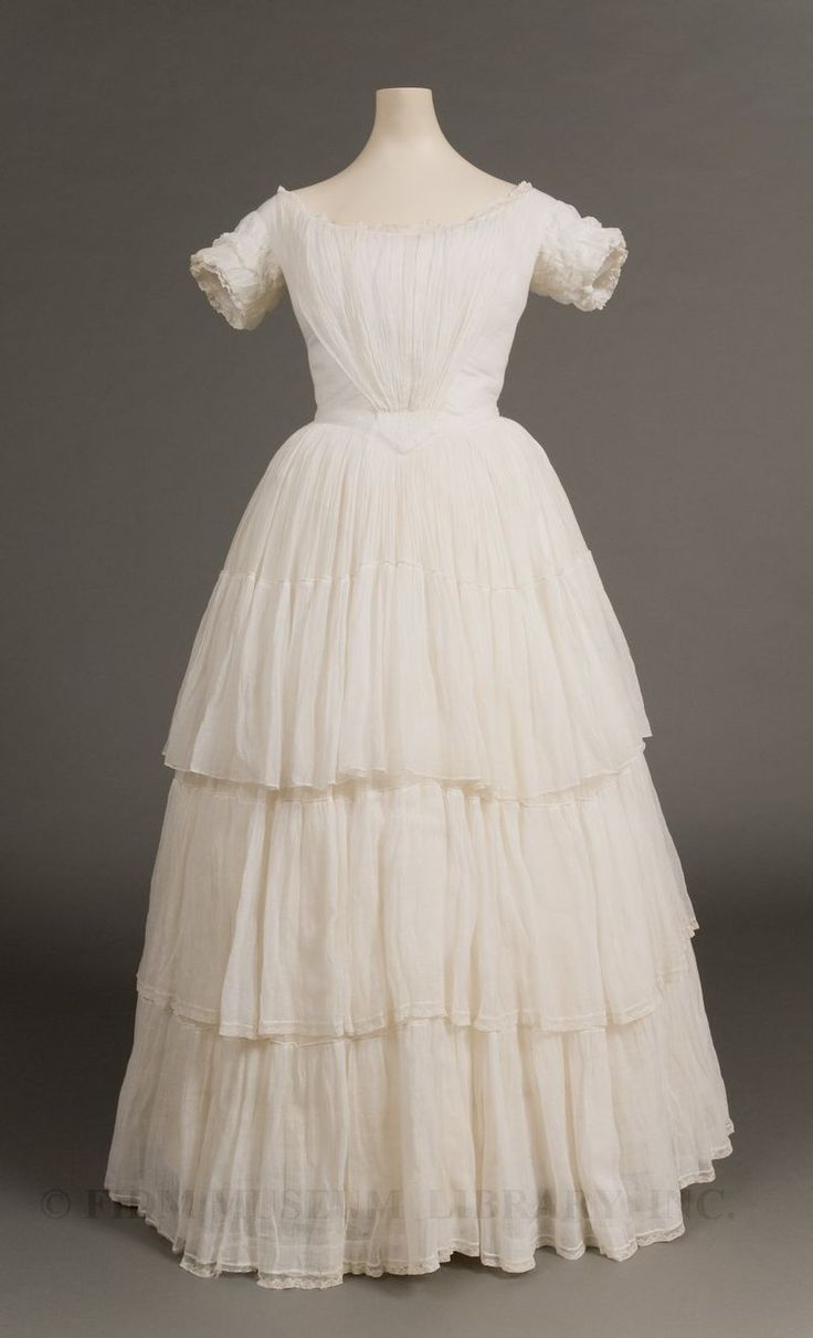 Muslin dress, c. 1845  The ideal 1840s woman was a delicate being. She was innocent, modest, sensitive to etiquette, possessed of softly rounded shoulders and had a demure gaze. This 1840s dress, made from diaphanous white cotton muslin edged with bobbin lace, suggests these qualities.