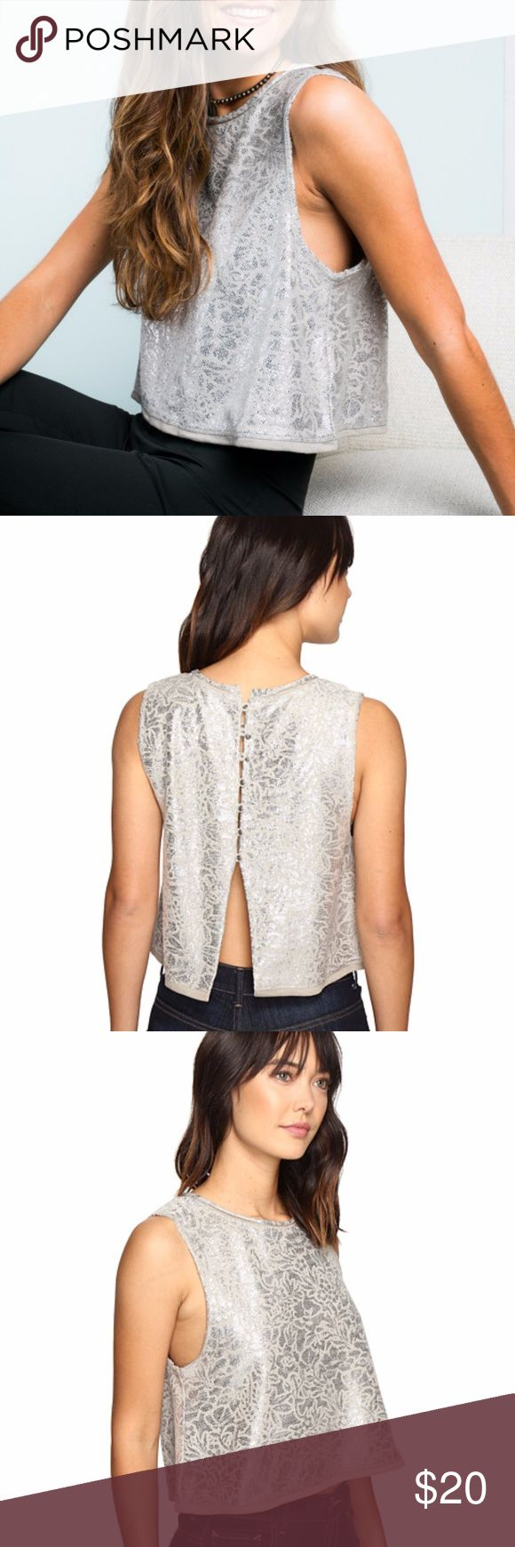 "Free People Casual Fancy Silver Crop Top New with tags!  A simple and swingy shape and dropped armholes put a casual finish on a shimmering cotton-blend top. The femme look fastens in back for a clean look in front. 19"" Length  Back button closures Scooped neck Sleeveless 80% cotton, 20% polyester Hand wash cold, dry flat Free People Tops Crop Tops"