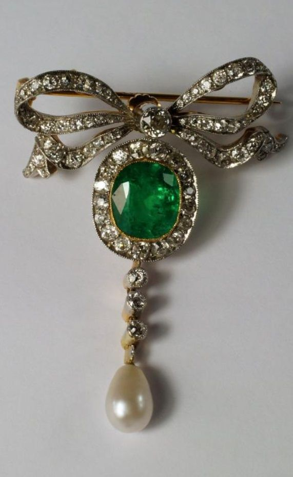 A Belle Epoch emerald, diamond and natural pearl brooch/pendant, early 20th century, the oval cut emerald cluster suspended beneath a diamond set bow, with three diamond and pearl drop below, the emerald approx 11mm x 10mm, the unmarked yellow metal pin and C clasp on removable screw fitting, the brooch with pendant suspension loops.
